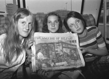 Drie vrouwen houden een krant op
